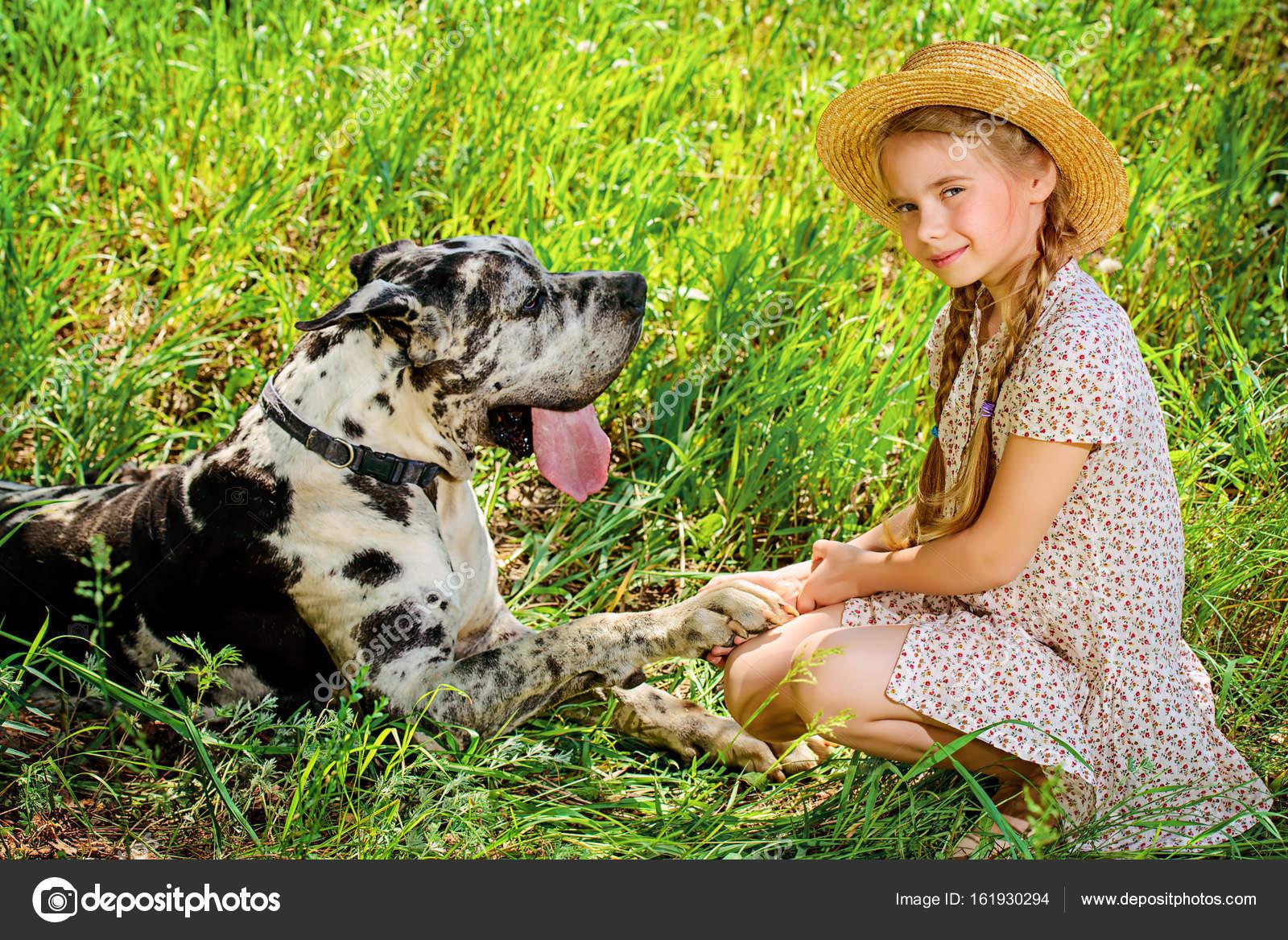 Feliz niña sostiene la pata de su perro. Amistad. Día soleado de verano en  el campo — Foto de prometeus 2405f225fa3