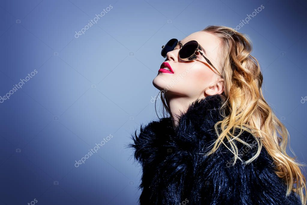 Attractive young woman wearing black sunglasses and fur coat. Studio shot. Beauty, fashion concept. stock vector