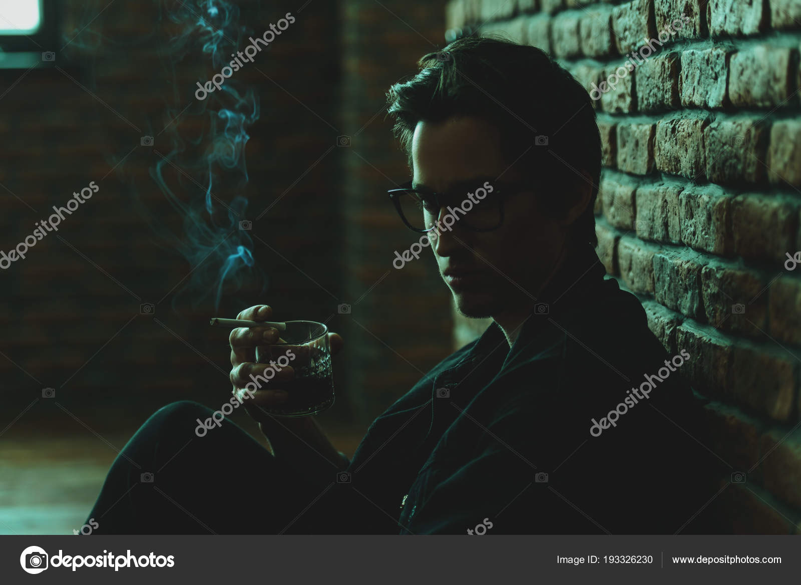 Attractive young man thoughtfully and calmly smoking a cigarette and drinking whiskey loft style interior mens beauty fashion optics style