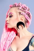 Fotografie Ohromující ženský model s růžový dredy pózuje na šedém pozadí. Trendy účesy. Krása, móda