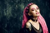 Fotografie Ohromující ženský model s růžový dredy pózuje na tmavém pozadí. Trendy účesy. Krása, móda