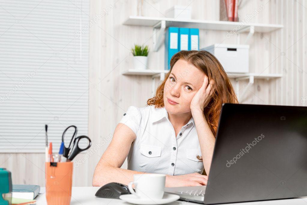Jeune réceptionniste assis derrière un bureau dans le bureau