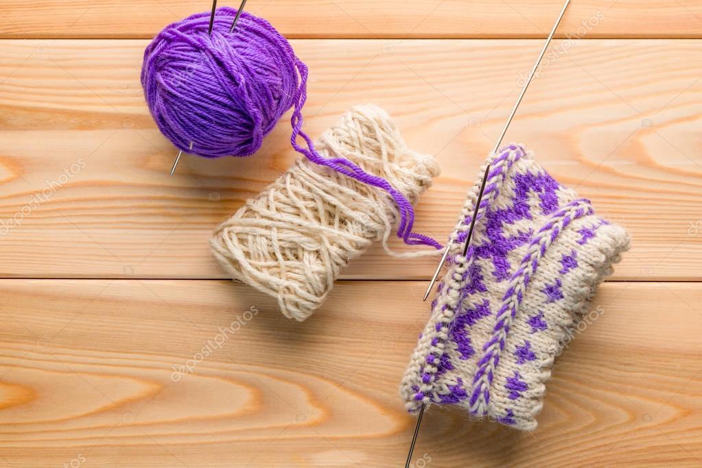hilado de lana morado y blanco y calcetines de punto con un patrón ...