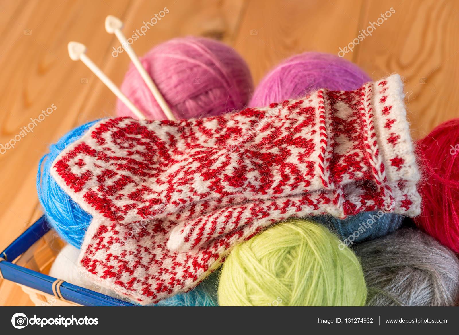 Fäustlinge mit schönen Muster handgefertigt liegen in den Wollfaden ...
