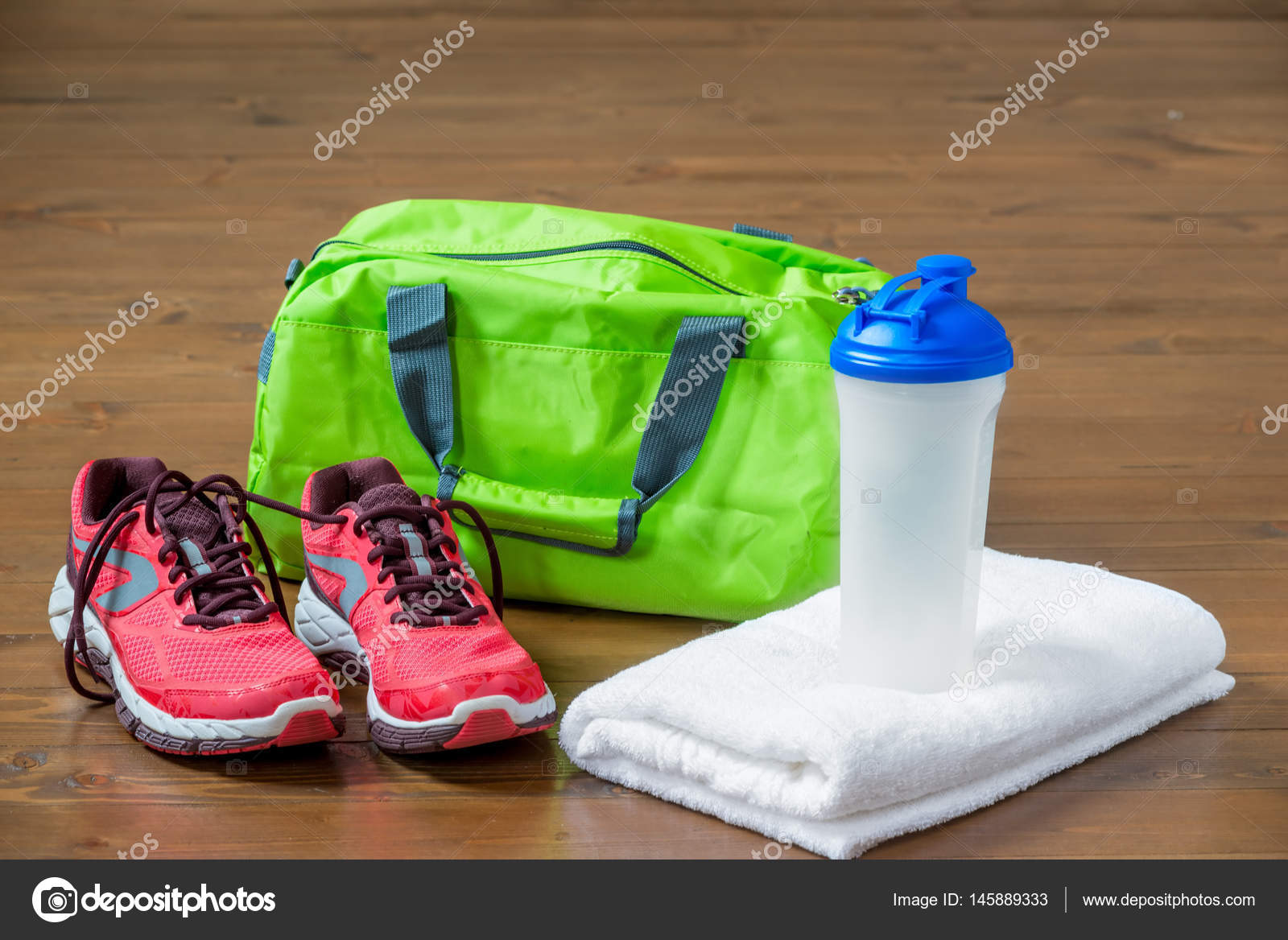 94eff90b47 Green sports bag and pink sneakers near a towel with a bottle fo — Stock  Photo