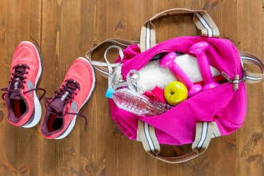 open sports bag and pink running shoes on a wooden floor top vie