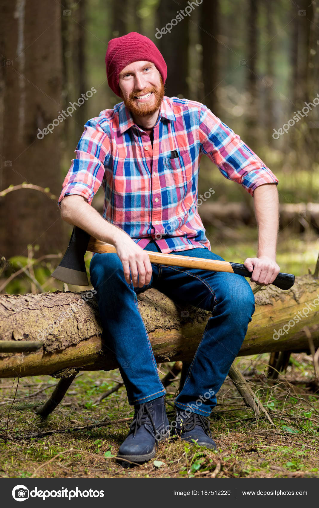 6d94c161d98 A smiling bearded lumberjack in a hat and shirt with an ax sits on a log in  the woods — Photo by ...