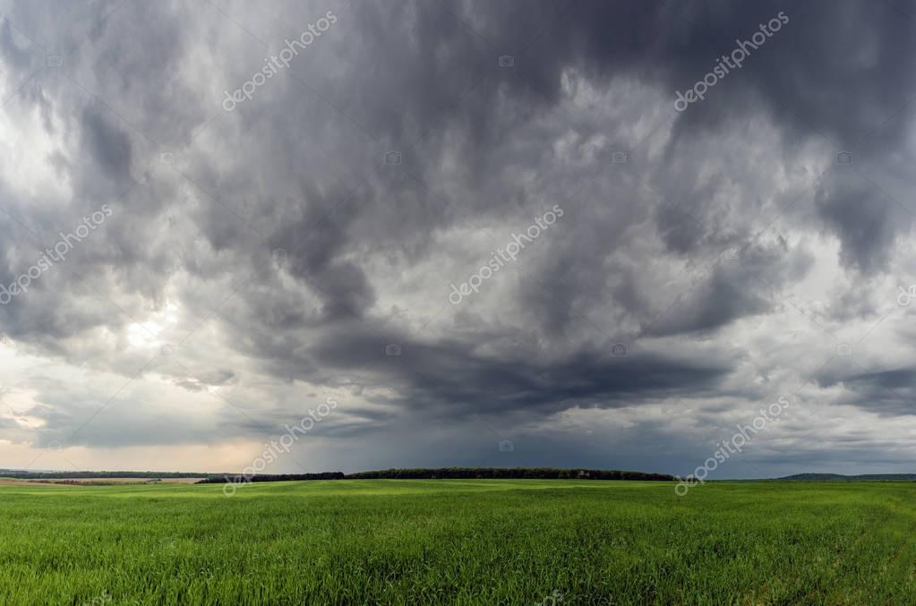 Dramatic storm scene with rain at the horizon and rural path going towards left