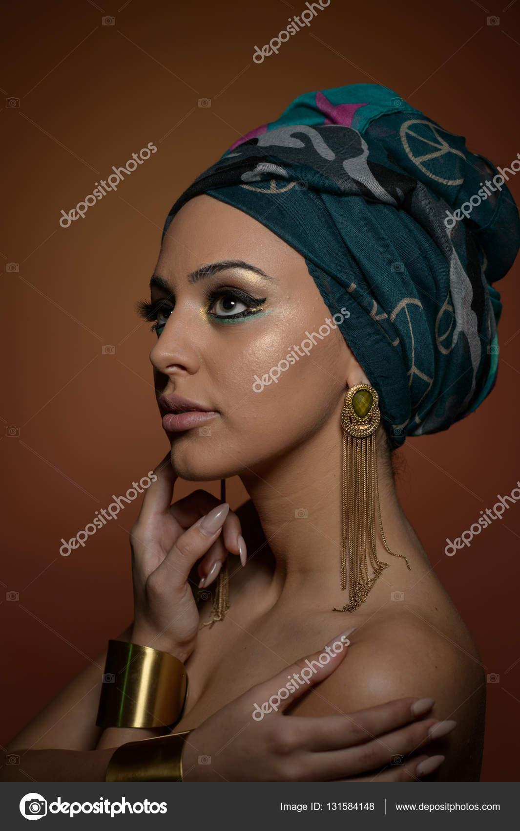 Gyönyörű nő egy turbán. Fiatal gyönyörű nő turbán és arany kiegészítők. Divatos  nő szépségét hajat turbán csomagolva. Szép kaukázusi modell visel fülbevaló  ... 31675e633e