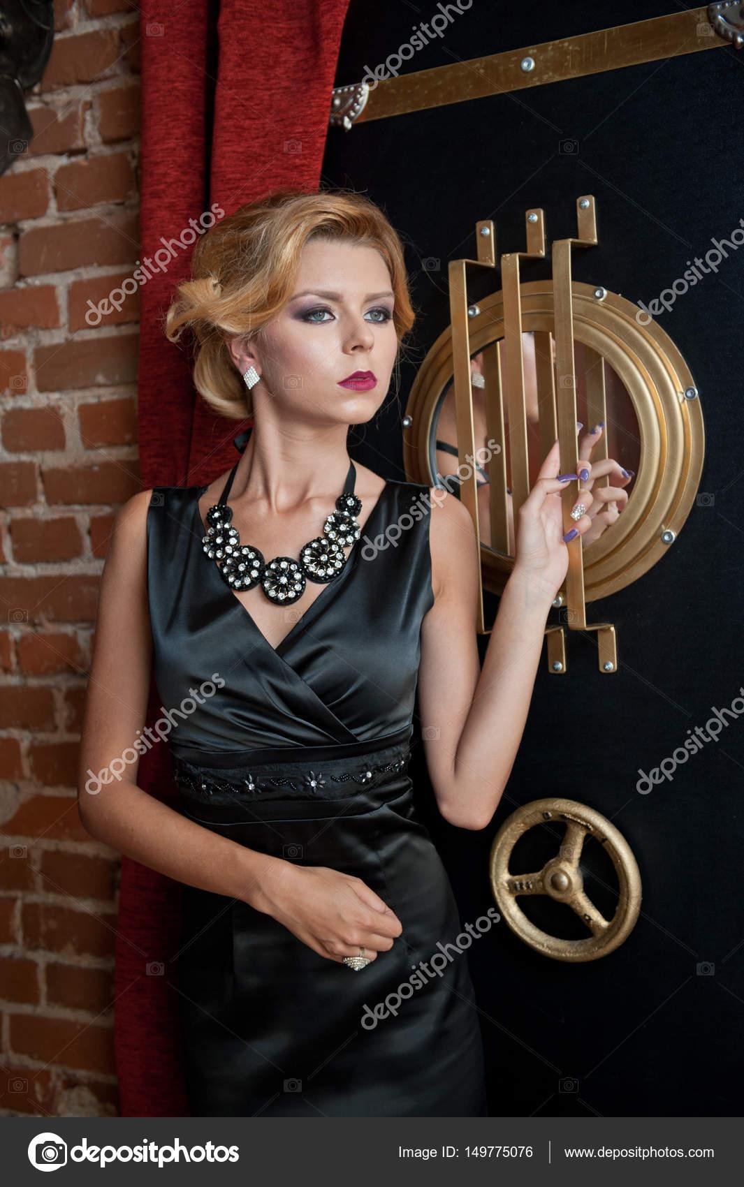85dd88c5d56 Модным чувственный привлекательной леди с Черное платье стоя возле Сейф в  старинных сцены. Короткие волосы блондинка с творческой стрижка и звезда  кино ...