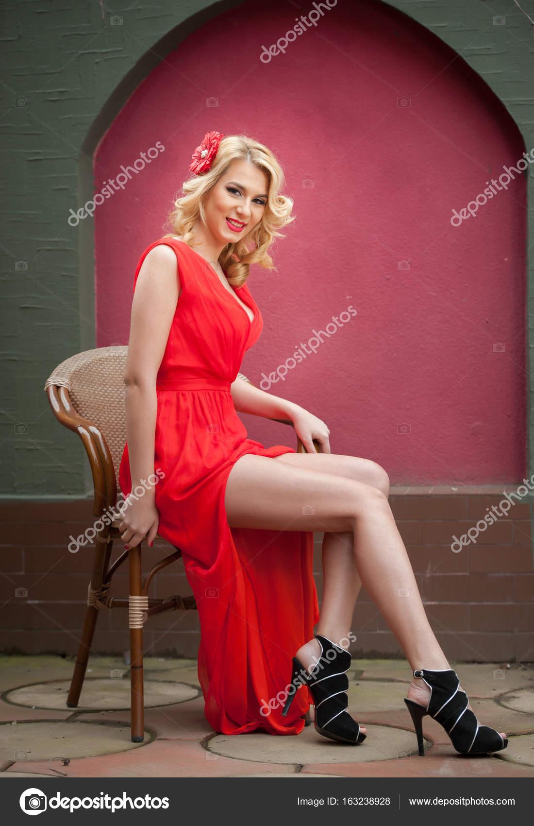 Moda mujer rubia atractiva en vestido rojo sentado en silla. Hermosa ...