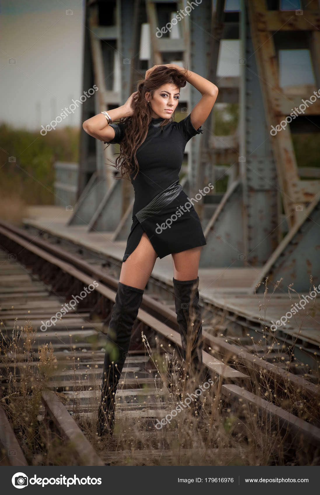 73765ee4635 Fashion sexy girl , on the bridge posing in black long boots on high heels–  stock image