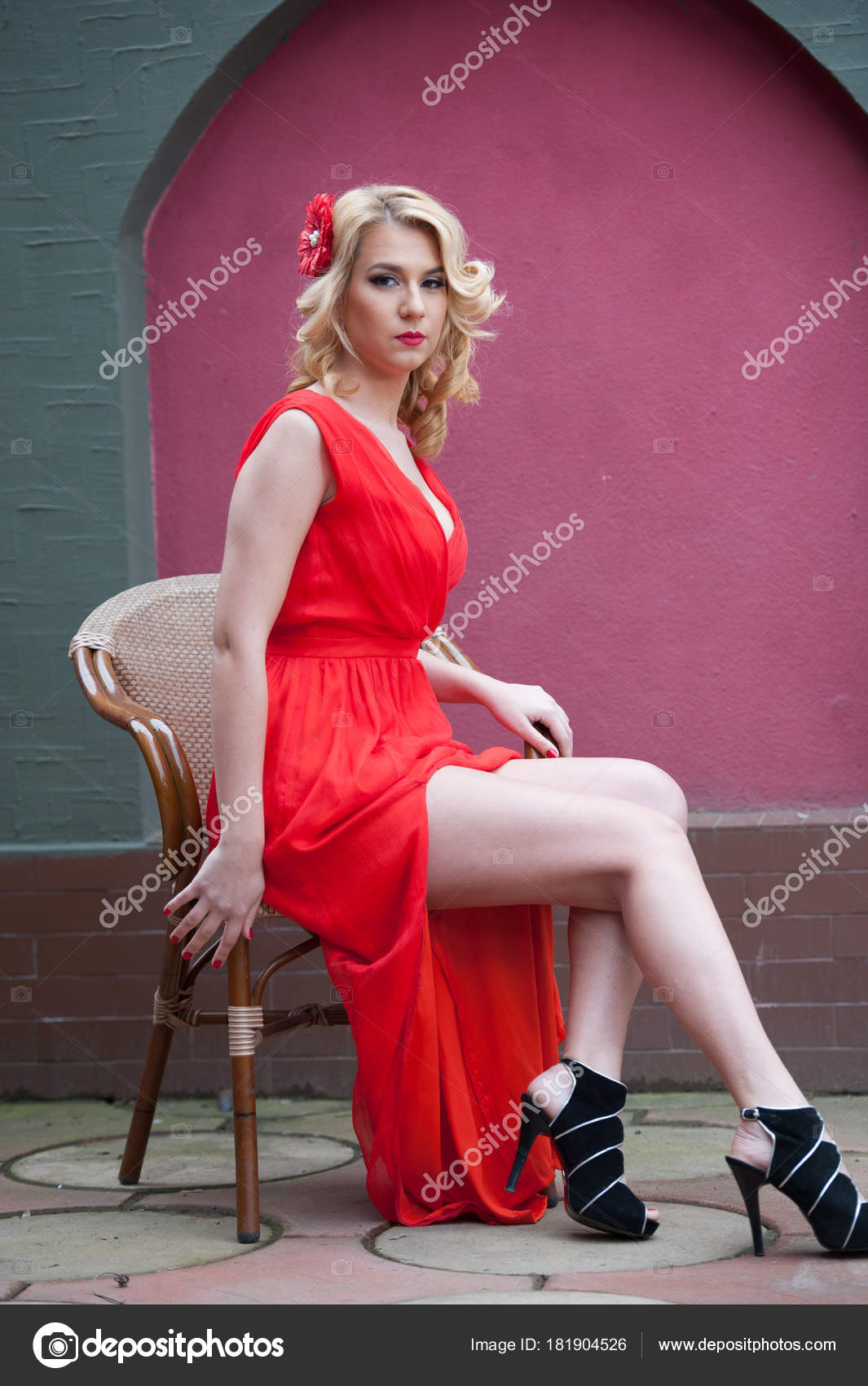 965a03ddf7a1 Donna bionda attraente alla moda in vestito rosso che si siede sulla sedia.  Bella donna elegante con il fiore rosso in capelli in posa in uno scenario  ...