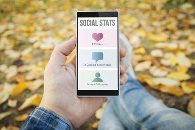 man in park cheking social stats