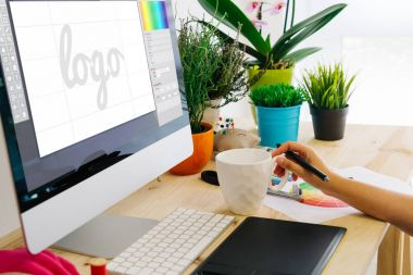 Graphic designer using pen tablet to design a logo. All screen graphics are made up. stock vector