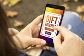 mobile marketing concept: woman using smartphone with gift voucher on screen