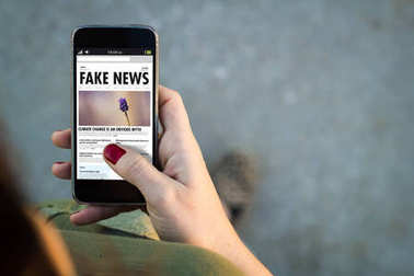 woman holding smartphone with fake news website on screen