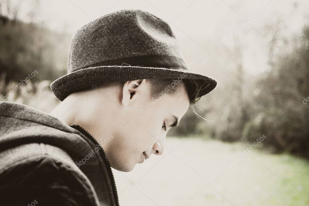 portrait of young sad man wearing hat outdoor
