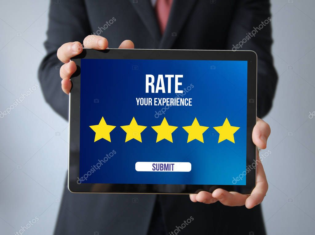review concept, businessman with rating interface on tablet pc. Screen graphics with text Rate Your Experience and stars icons