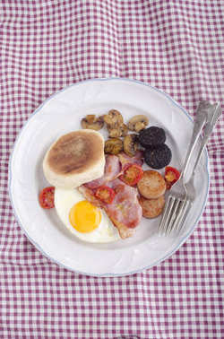 British Breakfast With Fried Egg, Black And White Pudding, Bacon, Tomato And Mushrooms On white Plate