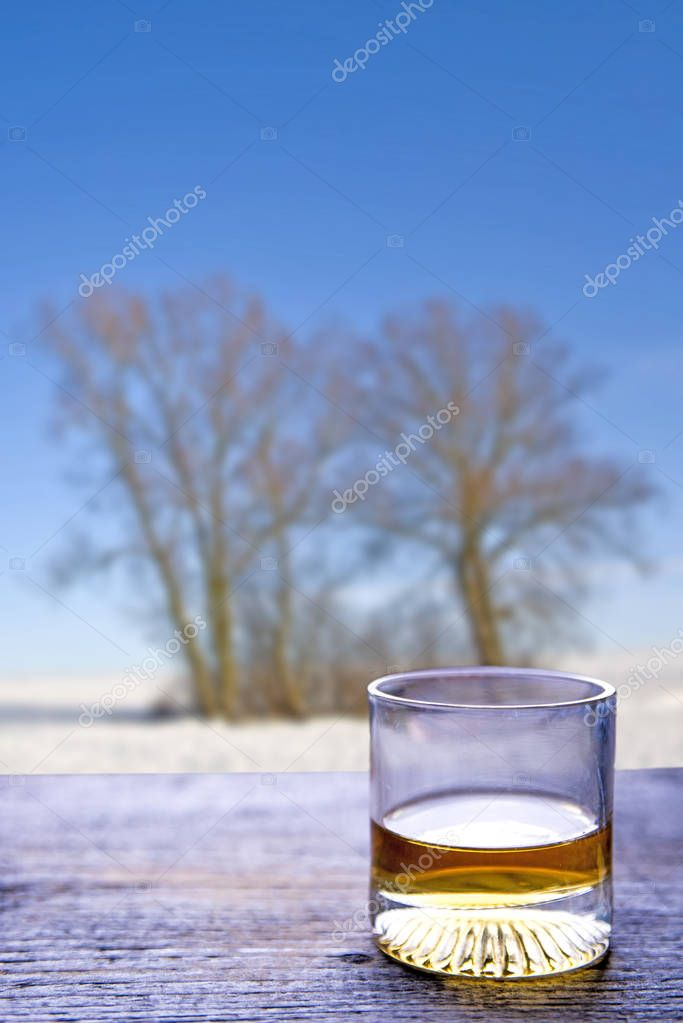 glass with whisky on window sill and winter landscape on background