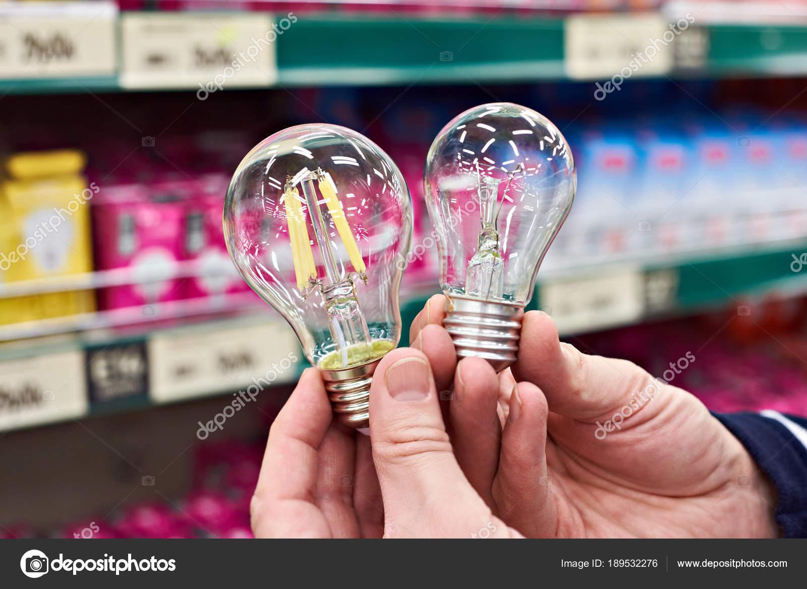 Lampe Led Et A Incandescence En Mains Sur Store Photographie