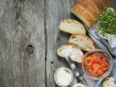 Fotografie Svěží francouzská bageta podávaný s kozím sýrem a lososem na dřevěný stůl