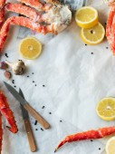 Photo Top view of fresh crab legs with lemons and spices on crumpled paper