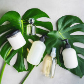 Fotografie Cosmetic set of blank label bottles for mockup packaging of skincare product cream, serum, oil, shampoo, conditioner, perfume on grey background with green leaves. Natural beauty product concept.
