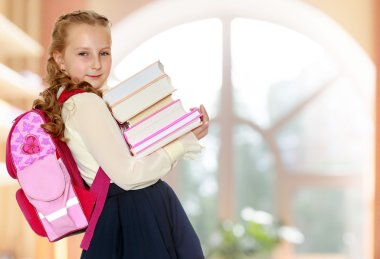 Girl schoolgirl with a satchel behind shoulders and books in han
