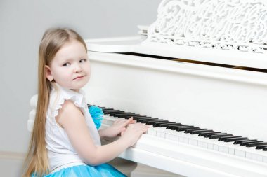 Little girl plays the piano.