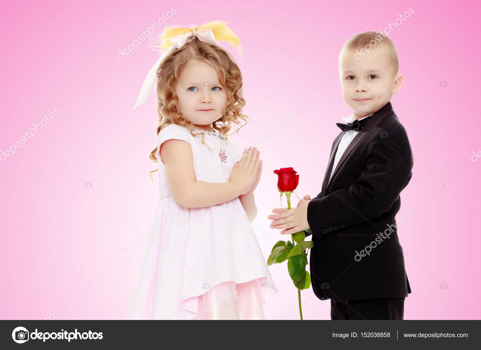 El muchacho le da a la niña una flor — Fotos de Stock © lotosfoto1 ...
