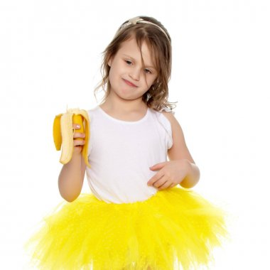 The little girl in the yellow skirt eating a banana.
