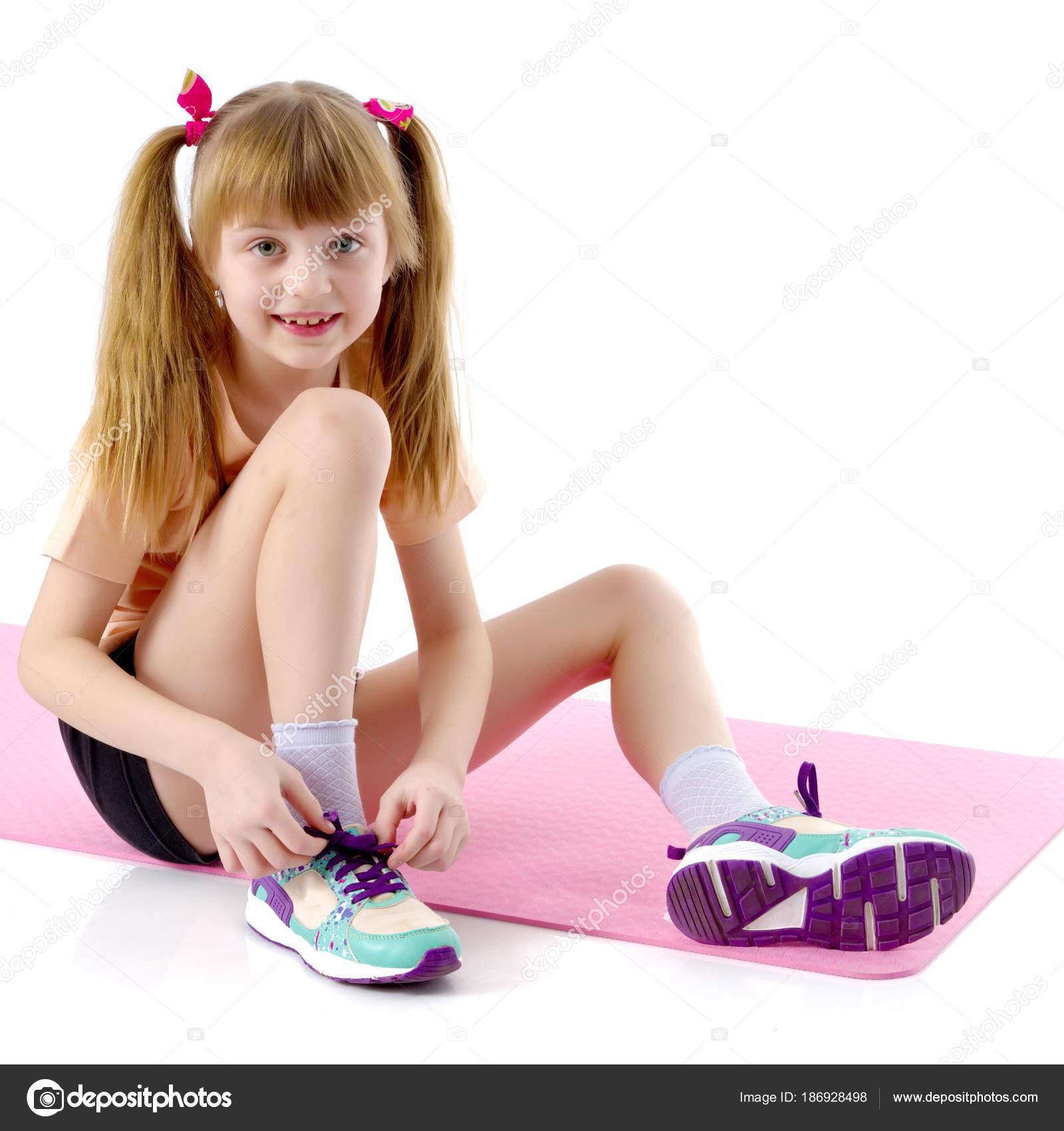 07d25eb9c5aad3 Das kleine Mädchen setzt auf ihre Schuhe — Stockfoto © lotosfoto1 ...