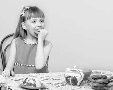 The girl drinks tea and eats the bread at the dinner table.