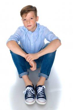 Fashionable boy teen sitting on the floor.