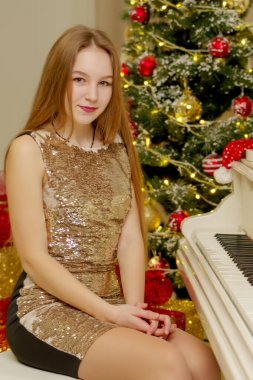 Teenage girl near the New Year tree behind the keys of a white p