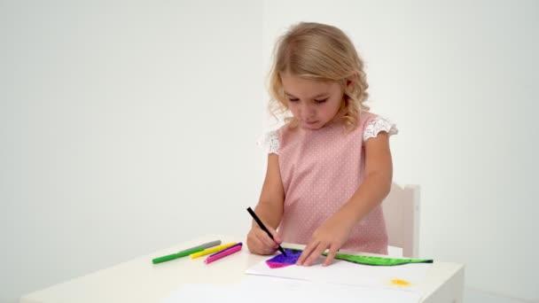 Egy kislány az asztalnál a rajz.