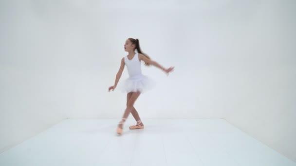 Charmantes kleines Mädchen in Bündel und Spitzenschuhen tanzt im Studio. Isoliert über weißem Hintergrund.