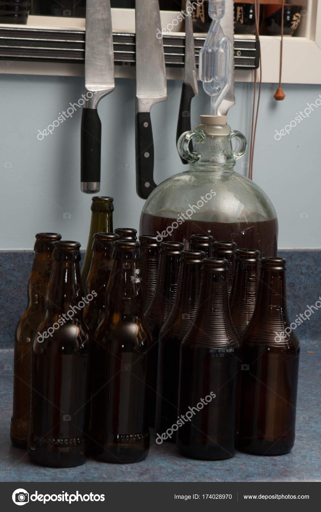 Vergorenen Bier in eine Korbflasche mit Schleuse und braune Flaschen ...