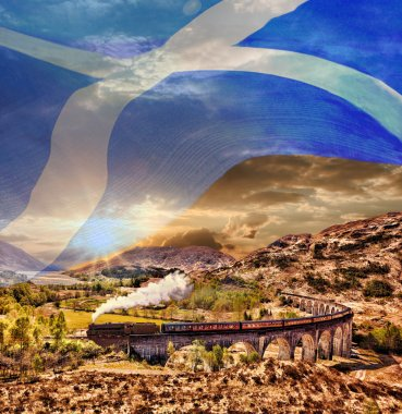 Glenfinnan Railway Viaduct in Scotland with the Jacobite steam train with scottish flag