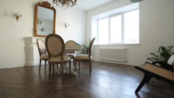 Bílý obývací pokoj s klasickou výzdobou, zrcadlo, krb, jídelní stůl