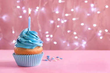 Birthday cupcake with burning candle on table against blurred lights
