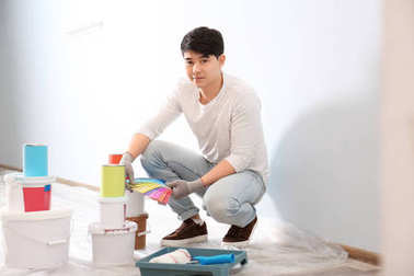Male decorator holding color palette samples on white background