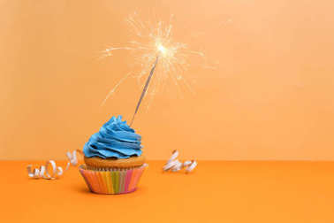 Birthday cupcake with sparkler on color background