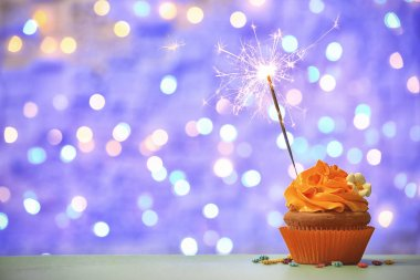 Birthday cupcake with sparkler against blurred lights