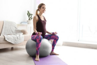 Young pregnant woman doing exercises with dumbbells at home