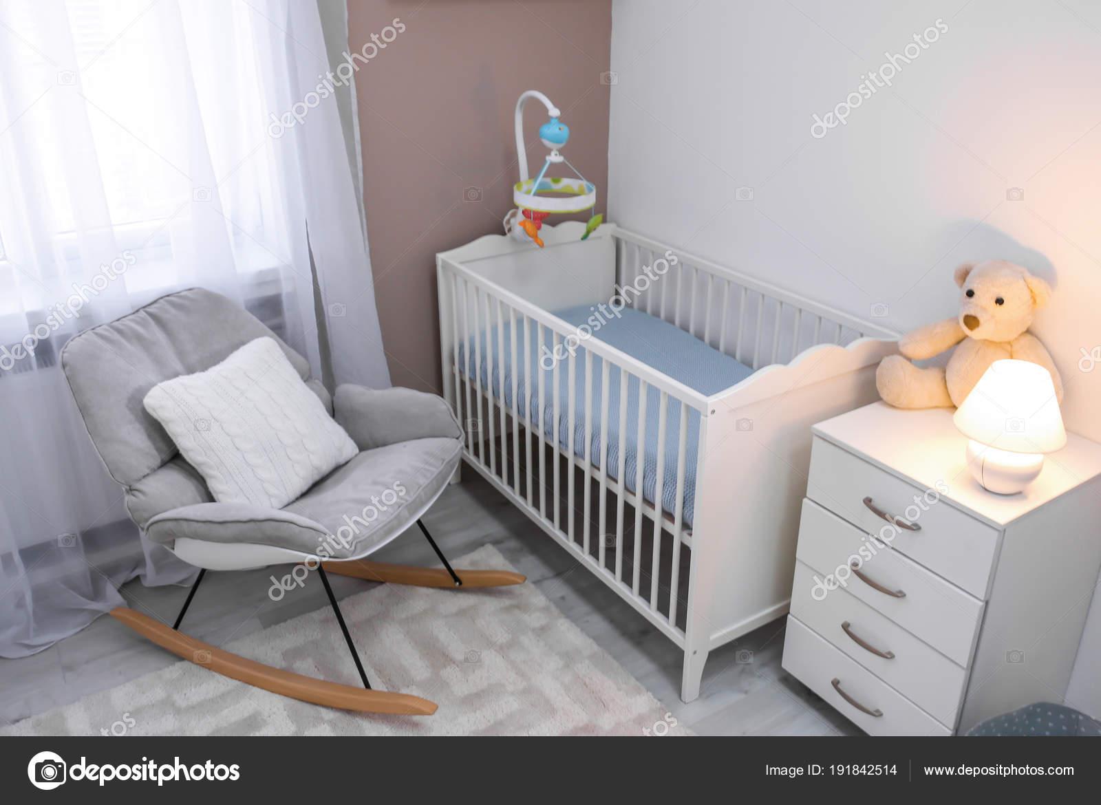 Gezellige baby kamer interieur met wieg en schommelstoel
