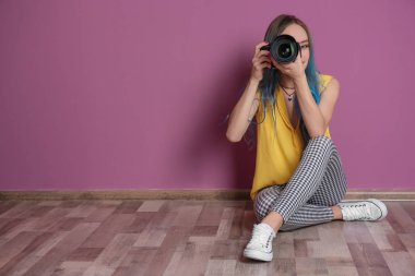 Young female photographer with camera near color wall