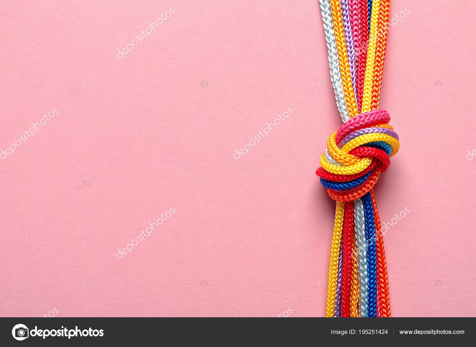 2fae68734c261 Des cordes différentes liées par noeud sur fond de couleur. Concept de  l'unité